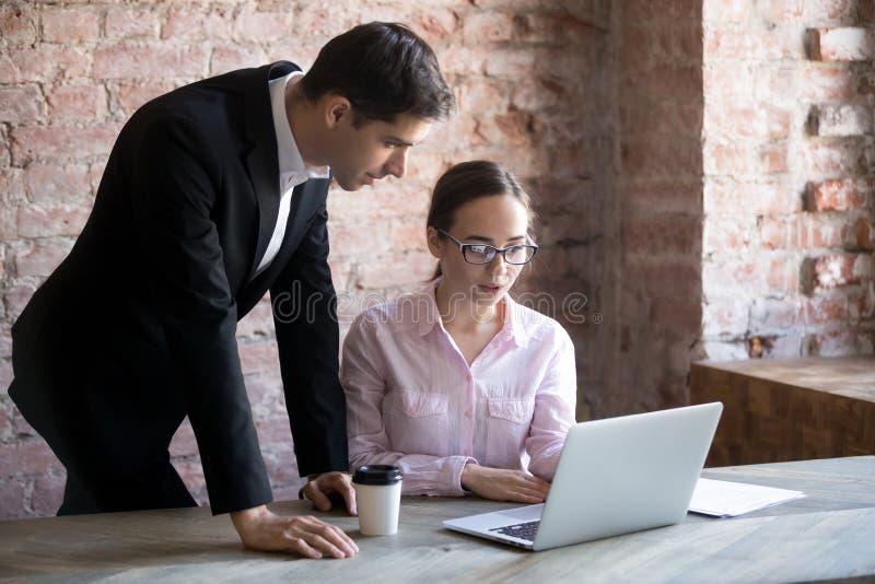 Geschäftsfrau erklärt Aufgabe Angestelltem, der Mann, der Laptop betrachtet, lizenzfreie stockbilder