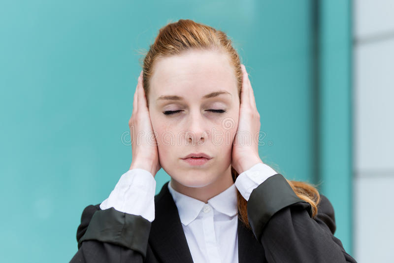 Geschäftsfrau-With Eyes Closed-Bedeckungs-Ohren stockfotos