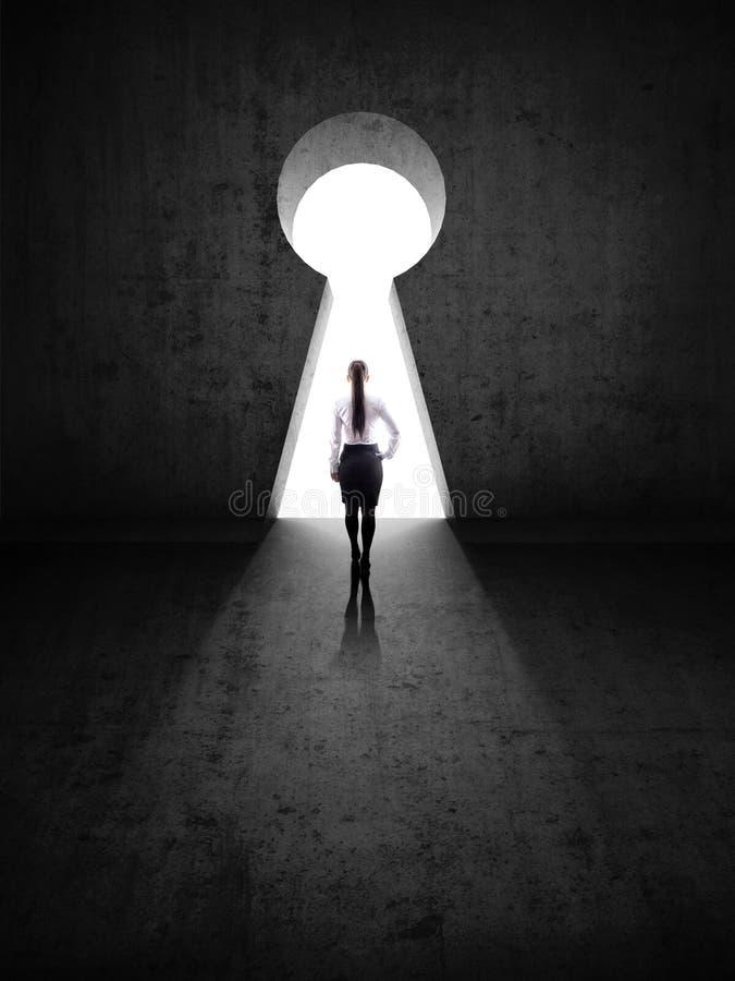 Geschäftsfrau gegen schwarze Wand mit Schlüsselloch stockfotografie