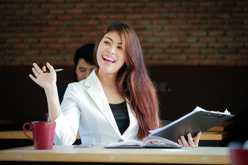 Geschäftsfrau Greet mit der Freude, die an der Kaffeestube arbeitet stockfoto