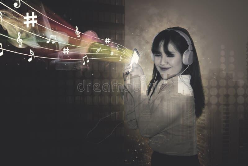 Geschäftsfrau hört Musik im Stadthintergrund stockfotografie