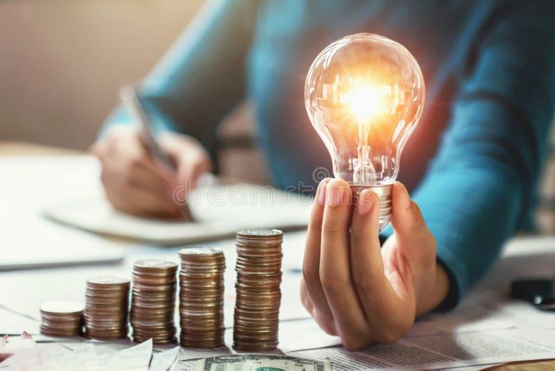 Geschäftsfrau-Handholdingglühlampe mit Münzenstapel auf Schreibtisch Konzepteinsparungsenergie lizenzfreie stockbilder