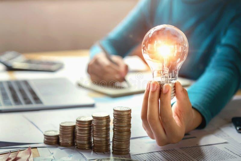 Geschäftsfrau-Handholdingglühlampe mit Münzenstapel auf Schreibtisch Konzepteinsparungsenergie lizenzfreies stockfoto