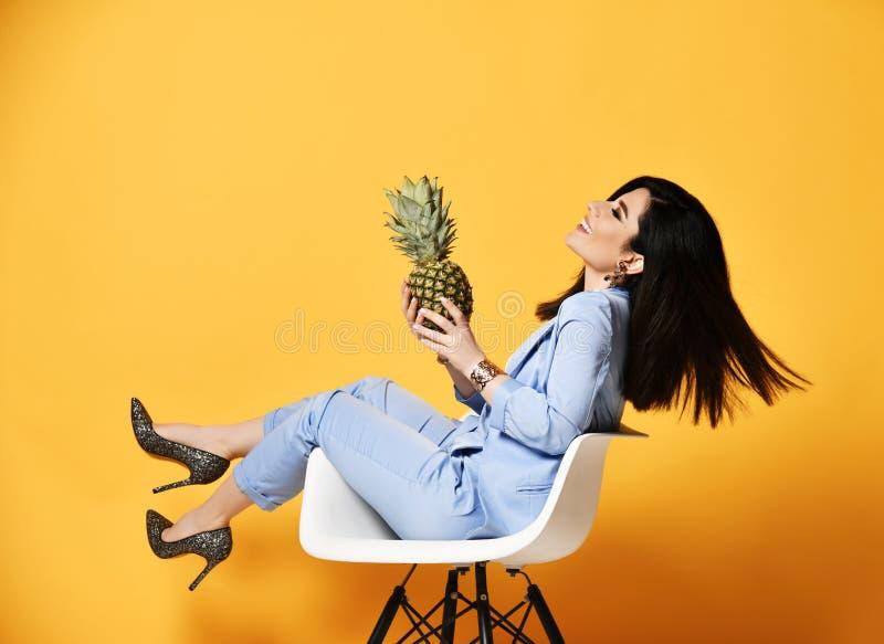 Geschäftsfrau-Holdingananas auf ihren offenen Palmen sitzt im Lehnsessel seitlich und im Lachen mit ihrem Kopf, der zurück geworf stockfotografie