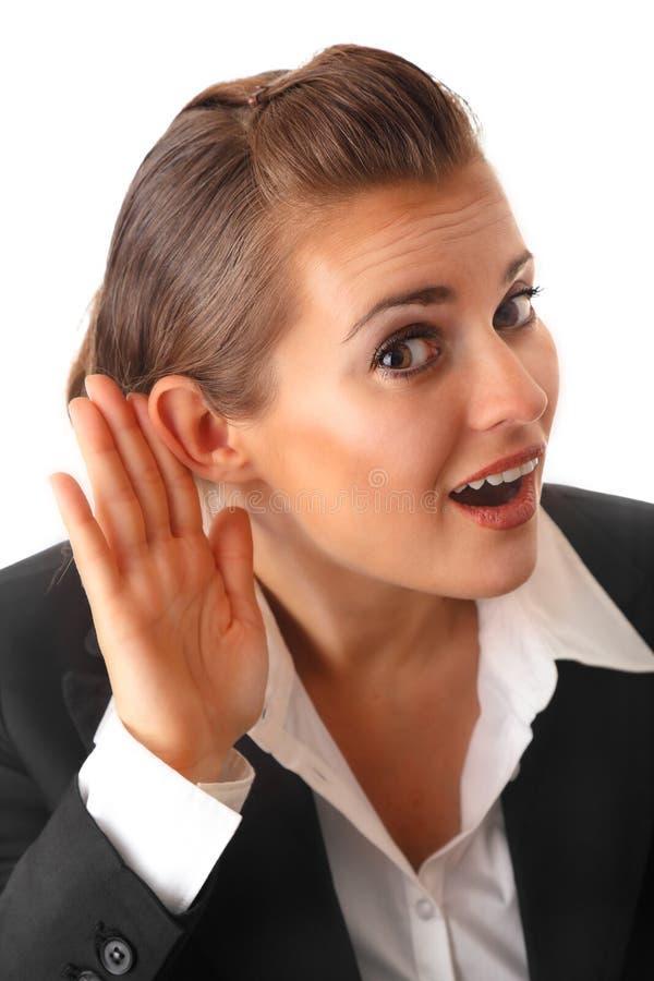 Geschäftsfrau-Holdinghand am Ohr und hören heimlich zu stockbilder