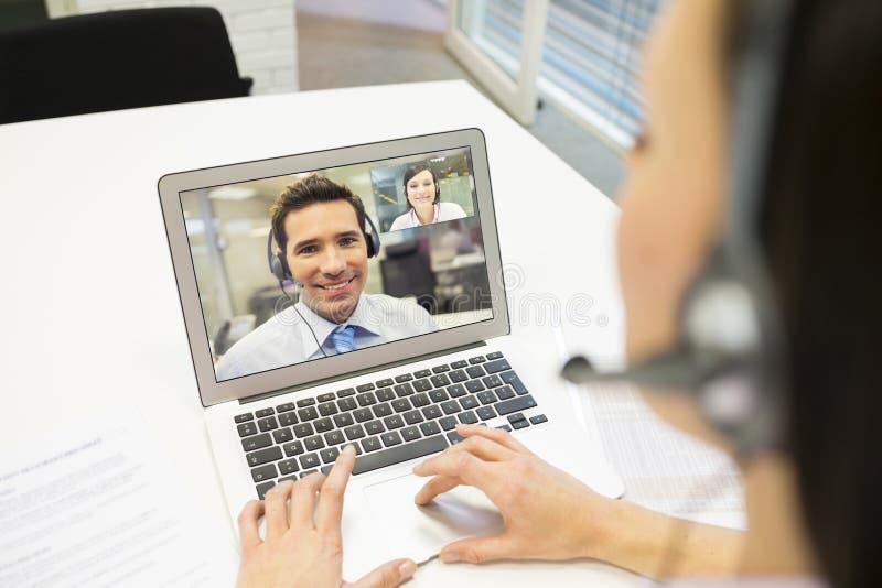 Geschäftsfrau im Büro auf Videokonferenz mit Kopfhörer, Himmel lizenzfreie stockfotografie