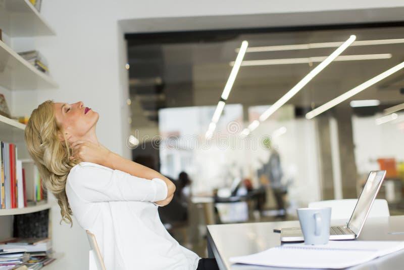 Geschäftsfrau im Büro, das eine Pause macht und eine Halsübung tut lizenzfreie stockfotos