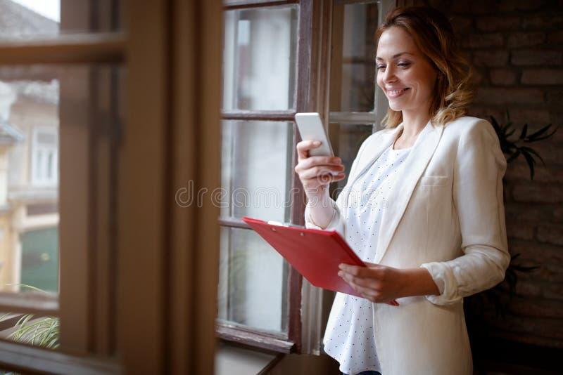 Geschäftsfrau im Büro, das mit Handy wählt lizenzfreie stockfotos