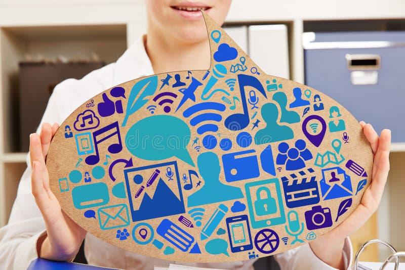 Geschäftsfrau im Büro mit Social Media-Ikonen lizenzfreie stockfotografie