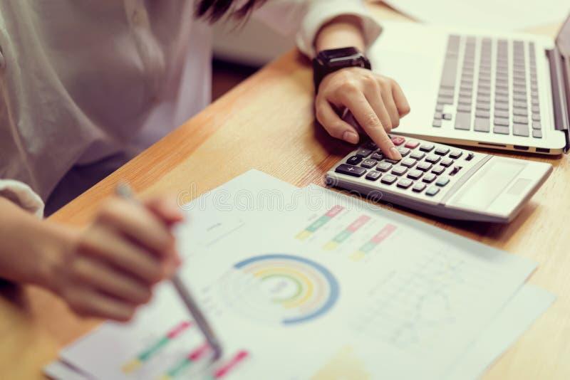 Geschäftsfrau im Büro und Gebrauchscomputer und -taschenrechner, zum von Finanzbuchhaltung durchzuführen lizenzfreie stockbilder