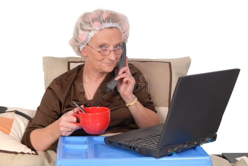 Geschäftsfrau im Bett, arbeitend stockfotografie