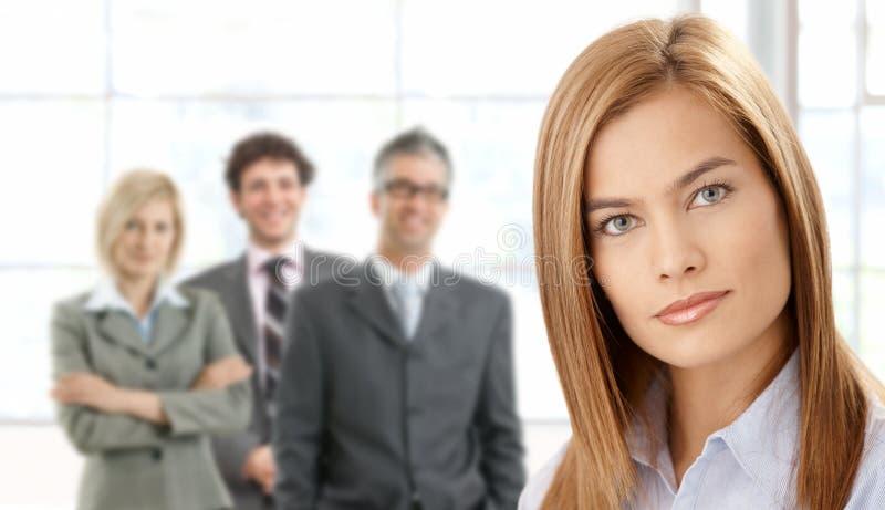 Geschäftsfrau im Fokus mit Team lizenzfreie stockfotografie