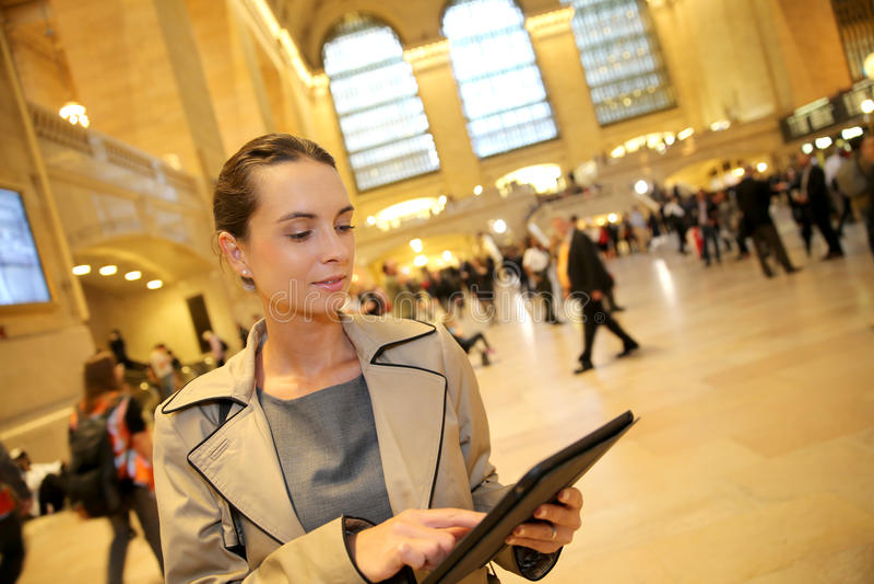 Geschäftsfrau im Hauptbahnhof mit Tablette lizenzfreies stockbild