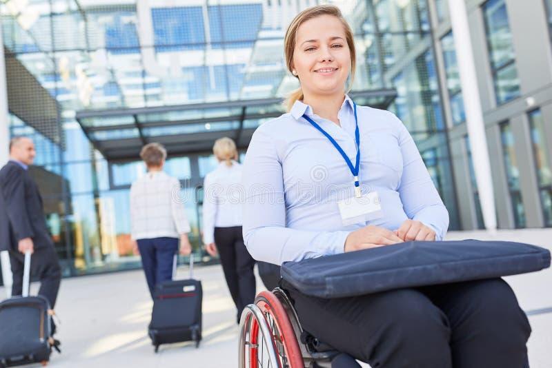 Geschäftsfrau im Rollstuhl bei Ankunft auf dem Kongress stockfotografie
