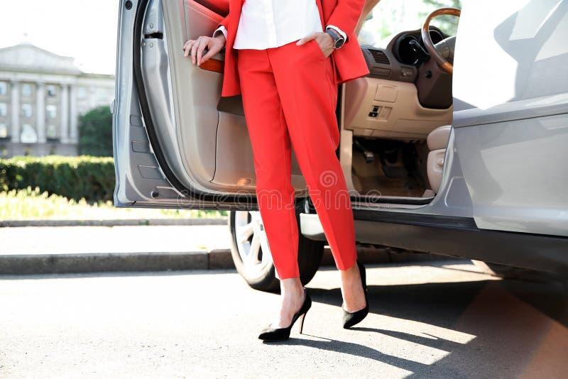 Geschäftsfrau im stilvollen Klagenverlassen ein Auto stockbild