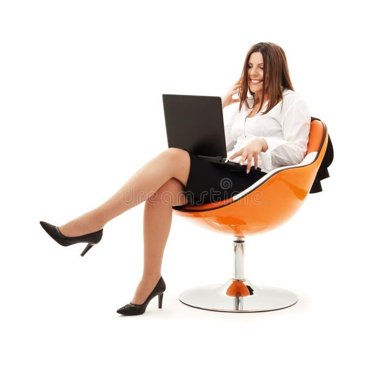 Geschäftsfrau im Stuhl mit Laptop lizenzfreies stockfoto