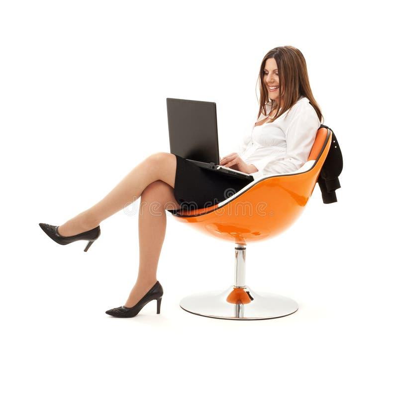 Geschäftsfrau im Stuhl mit Laptop stockbild