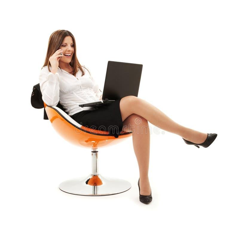 Geschäftsfrau im Stuhl mit Laptop und Telefon stockfoto
