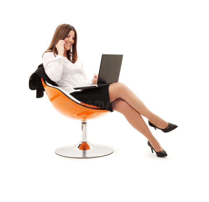 Geschäftsfrau im Stuhl mit Laptop und Telefon lizenzfreies stockbild