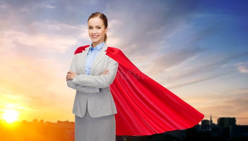 Geschäftsfrau im Superheldkap über Stadtsonnenuntergang lizenzfreie stockfotografie