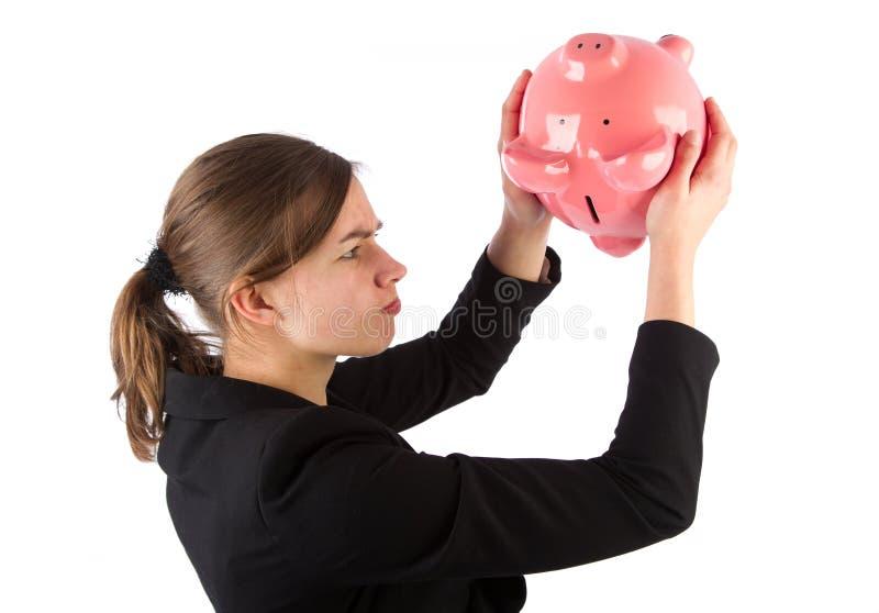 Geschäftsfrau ist nicht imstande, Geld aus piggy Querneigung heraus zu erhalten stockfoto