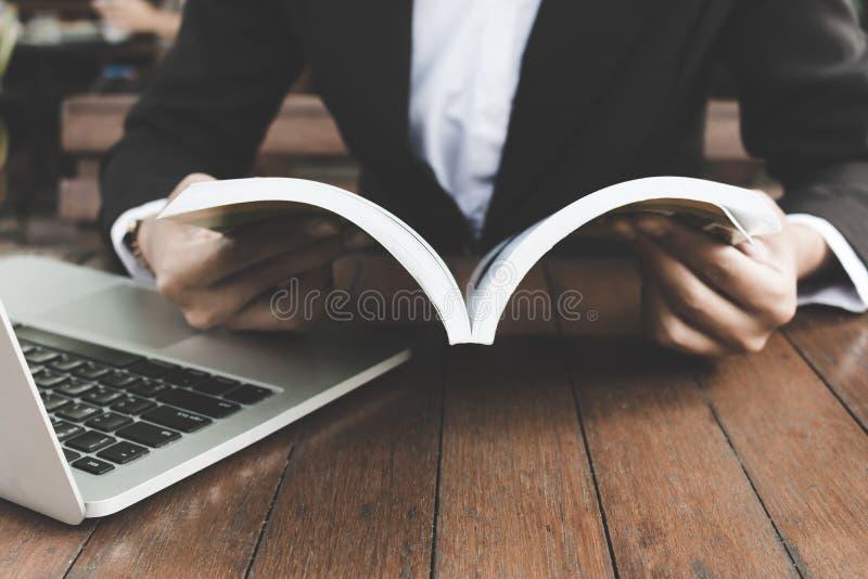 Geschäftsfrau las Buch und das Arbeiten im Kaffeestubedunkelheitston lizenzfreie stockbilder