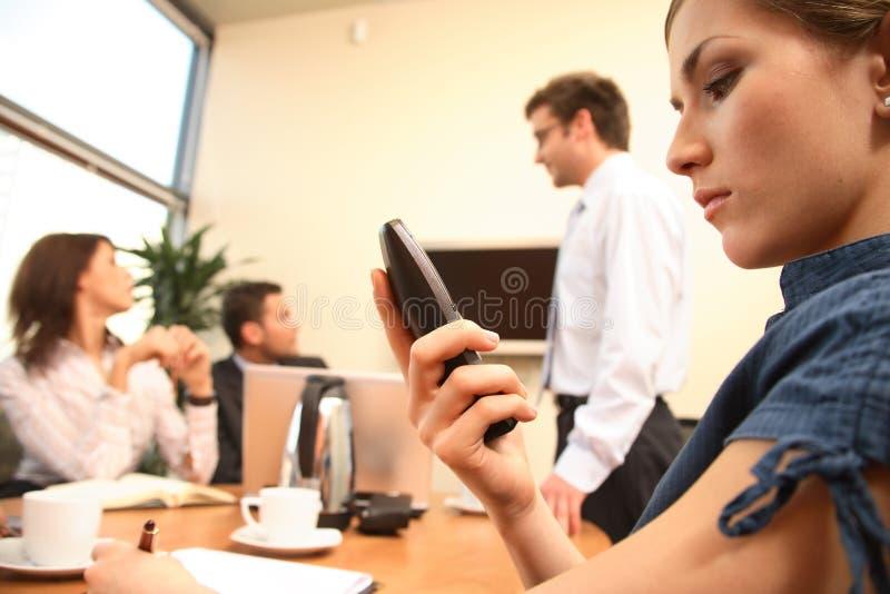 Geschäftsfrau-Lesemeldung auf Handy. Darstellung im Hintergrund. stockbild