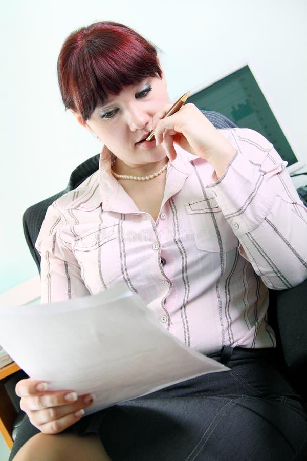 Geschäftsfrau liest Dokumente lizenzfreie stockfotos