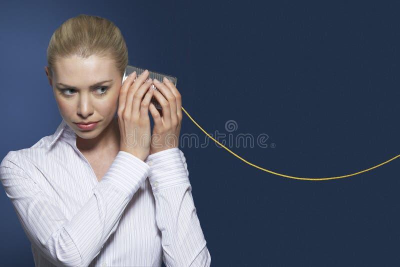 Geschäftsfrau Listening To Tin Can Phone lizenzfreies stockbild