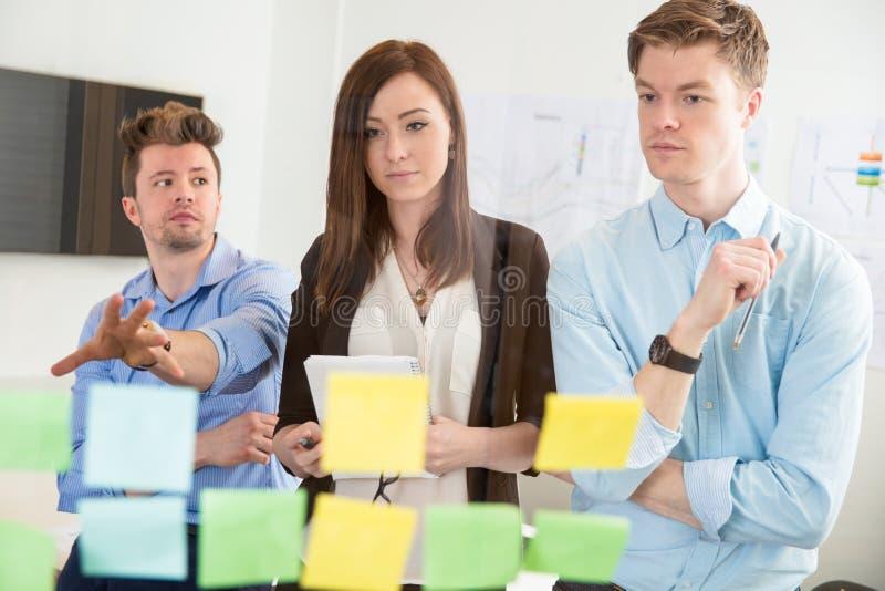 Geschäftsfrau Looking At Strategies auf klebenden Anmerkungen durch Colleag lizenzfreie stockfotografie