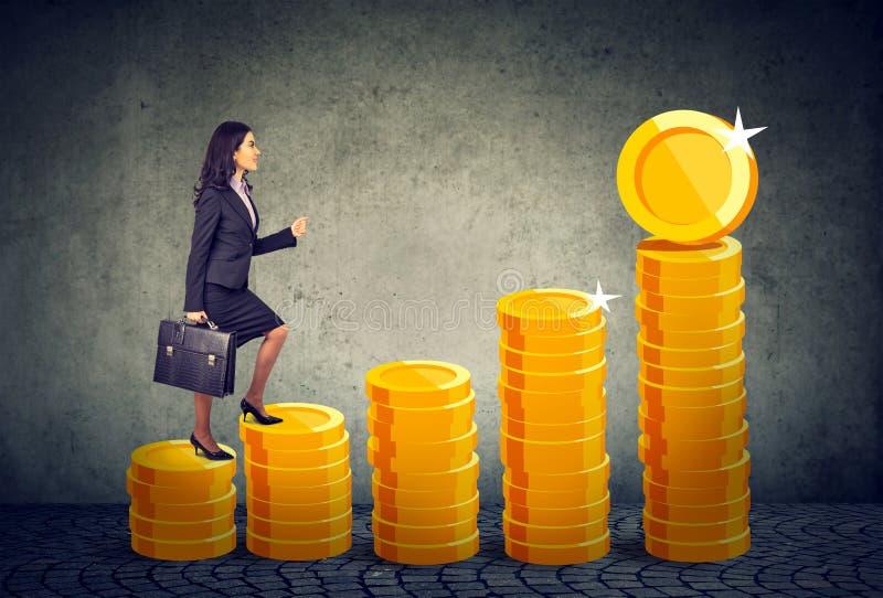 Geschäftsfrau mit Aktenkoffer eine Finanztreppenhausleiter steigernd gemacht von den Goldmünzen stockbilder