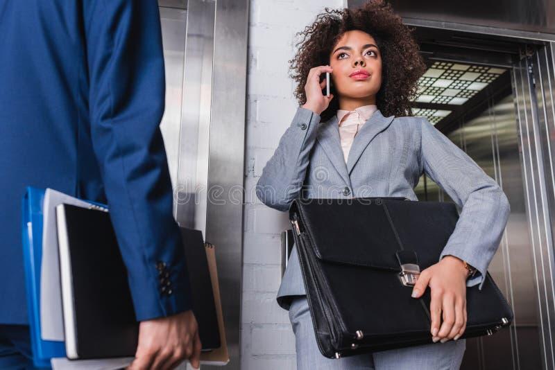 Geschäftsfrau mit Aktenkoffer sprechend am Telefon nahe bei Mann lizenzfreies stockfoto