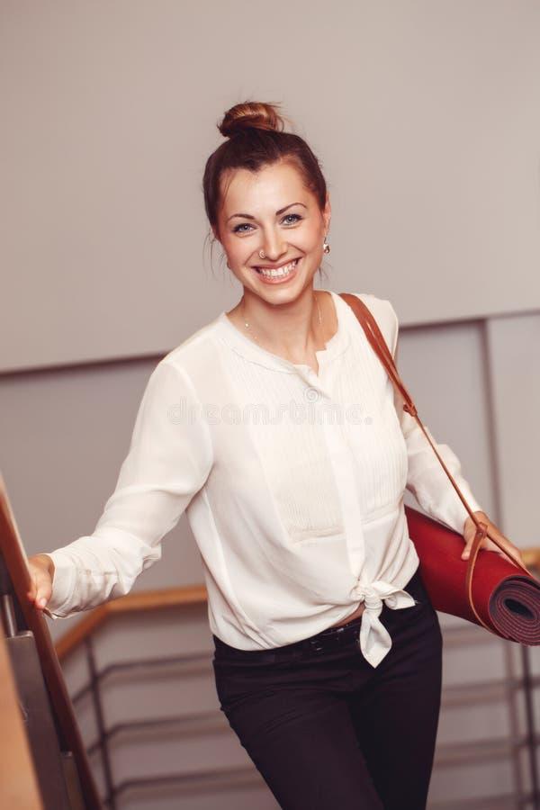 Geschäftsfrau mit blauen Augen im weißen in den haltenen Blusenhemd und schwarzen Hosen, tragende Yogamatte im Büro lizenzfreie stockfotografie