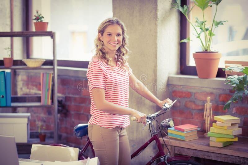 Geschäftsfrau mit dem Fahrrad, das im Büro steht stockbild