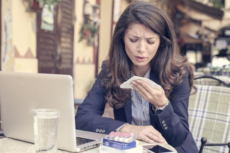 Geschäftsfrau mit dem kranken Arbeiten am Café lizenzfreie stockfotografie