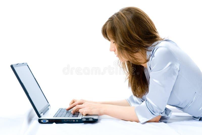 Geschäftsfrau mit dem Laptop, der auf dem Fußboden liegt. stockfoto