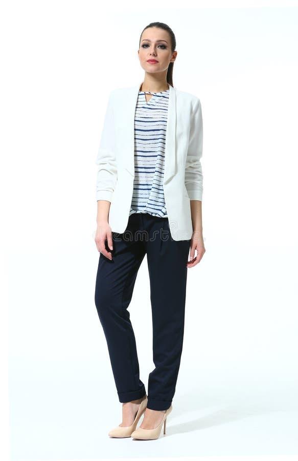 Geschäftsfrau mit dem Pferdeschwanz in der zufälligen weißen Jacke und in der schwarzen Hose lizenzfreies stockbild