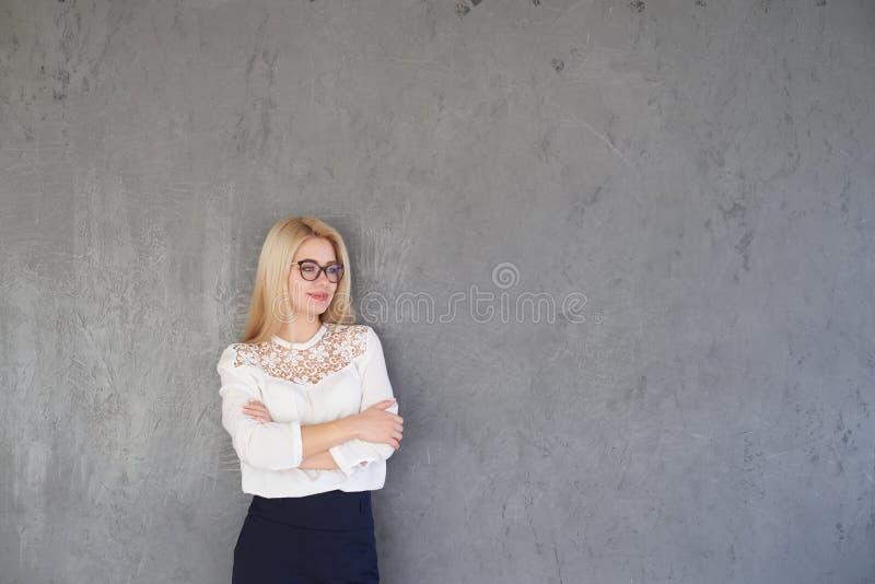 Geschäftsfrau mit den Armen gekreuzt gegen grauen Hintergrund stockfotografie