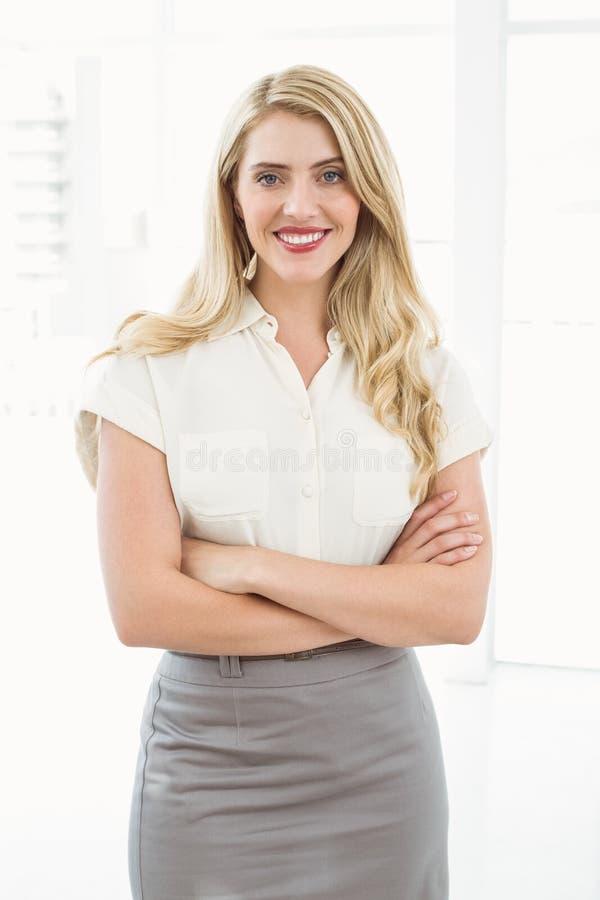 Geschäftsfrau mit den Armen gekreuzt im Büro lizenzfreie stockbilder