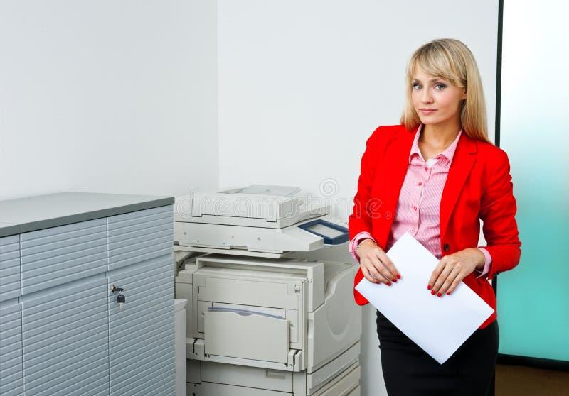 Geschäftsfrau mit den Dokumenten, die nahe bei Drucker stehen lizenzfreie stockfotos