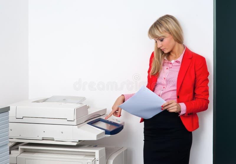 Geschäftsfrau mit den Dokumenten, die nahe bei Drucker stehen stockfoto