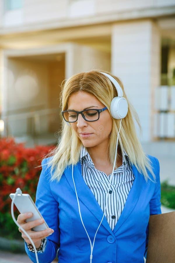 Geschäftsfrau mit den Kopfhörern, die beweglich schauen lizenzfreie stockfotos