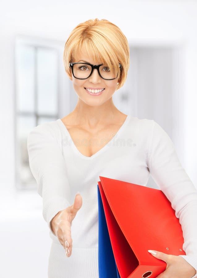 Geschäftsfrau mit den Ordnern bereit zum Händedruck stockfotos