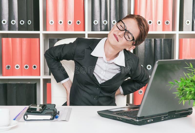 Geschäftsfrau mit den Schmerz in ihr zurück lizenzfreies stockfoto