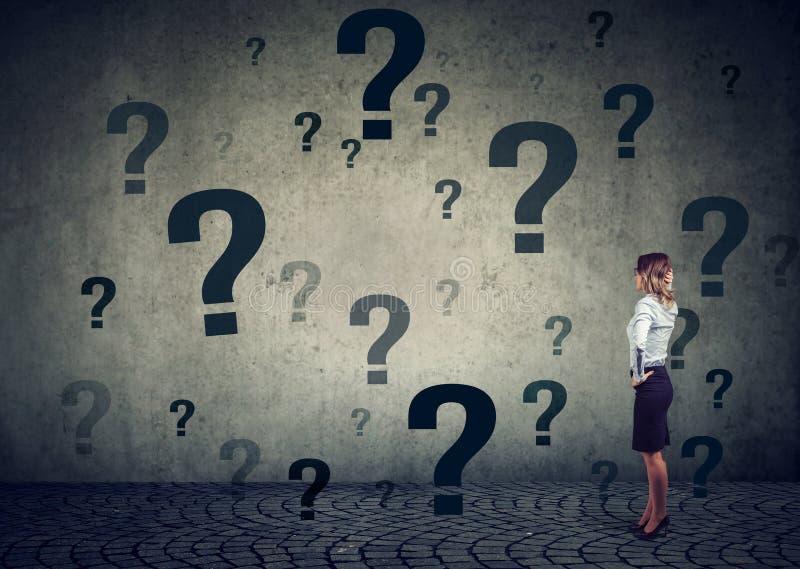 Geschäftsfrau mit der Hand auf dem Kopf, der vor einer Wand mit vielen Fragen steht stockfoto