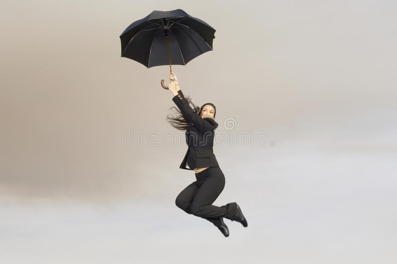 Geschäftsfrau mit einem Regenschirm im mitten in der Luft stockbild