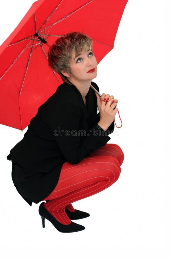Geschäftsfrau mit einem roten Regenschirm lizenzfreies stockbild
