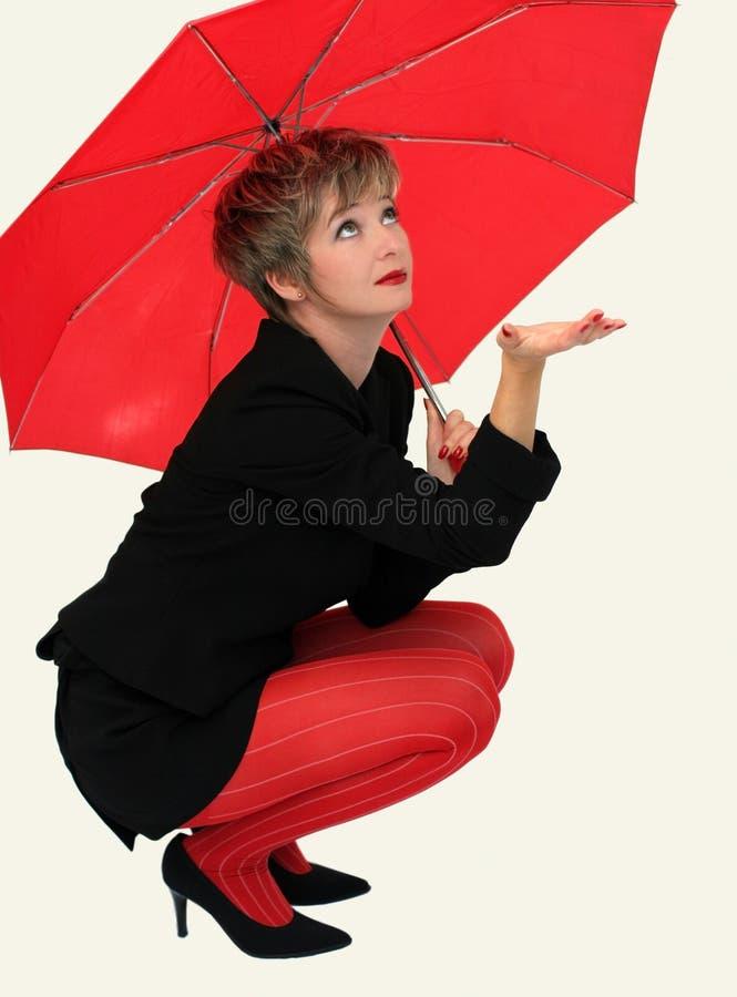 Geschäftsfrau mit einem roten Regenschirm lizenzfreies stockfoto