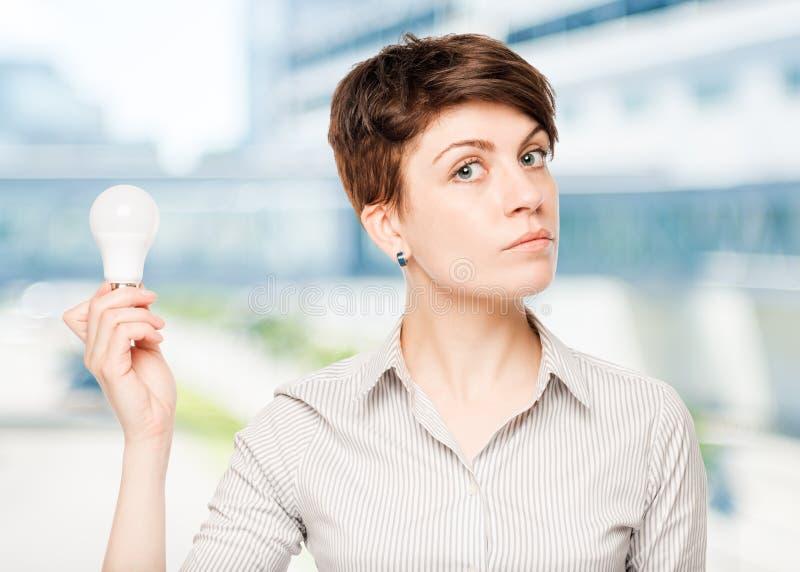 Geschäftsfrau mit einer Glühlampe in der Hand stockfotos
