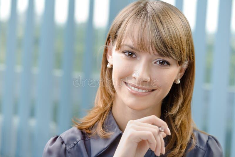 Geschäftsfrau mit Feder im Büro lizenzfreie stockfotos